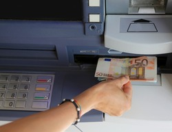 woman's hand takes money from the ATM in Europe