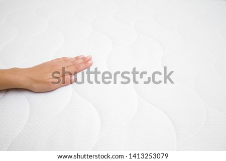 Woman's hand touching cloth of white mattress. Checking softness. Choice of the best type and quality. Side view. Closeup. Copy space. Empty place for text or logo.