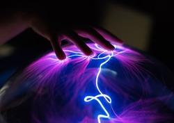 Woman's hand touching plasma globe.