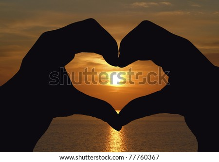 Woman's hand united forming a heart shape symbol at sunset