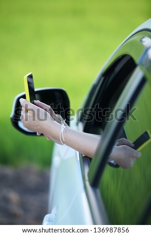 woman's hand using smart phone outside window car,conceptual for holiday,relax,navigator.