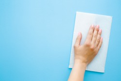 Woman's hand wiping pastel blue desk with white paper napkin. General or regular cleanup. Close up. Empty place for text or logo.