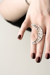 Woman's hand with a big openwork silver ring. Handmade statement jewelry.