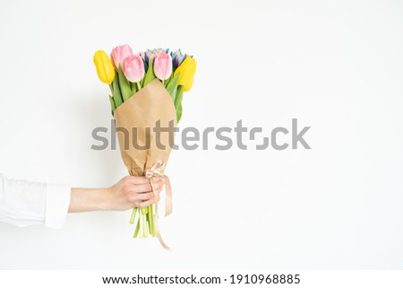 Woman's hand with a bouquet of colorful tulips against white wall Stock photo ©