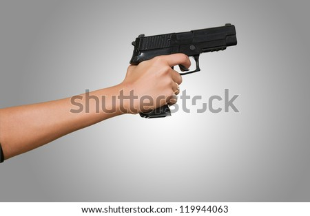Woman's Hand With A Gun against a grey background
