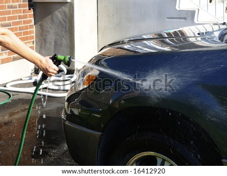 Woman's hand with a hose washing a car