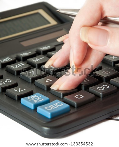 Woman's hand with a pen and calculator