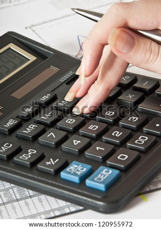 Woman's hand with a pen, calculator and the financial report