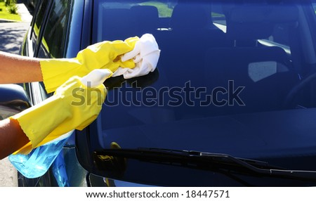 Woman's hand with a rag and glass cleaner washing windshield glass of an SUV car