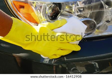 Woman's hand with a rag washing headlights of an SUV car