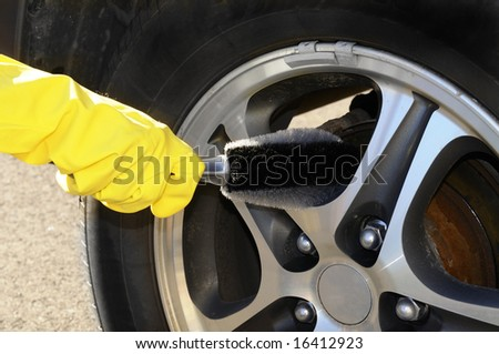 Woman's hand with a rim brush cleaning a wheel of an SUV car #16412923
