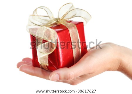 Woman's hand with a small red gift box with gold ribbon isolated on white background