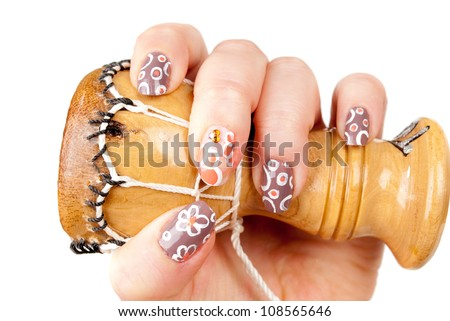 Woman's hand with  african tam tam and  manicure  on the white background.