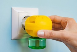 Woman's hand with an electric anti mosquito diffuser or repellent. Electric fumigator in the socket.