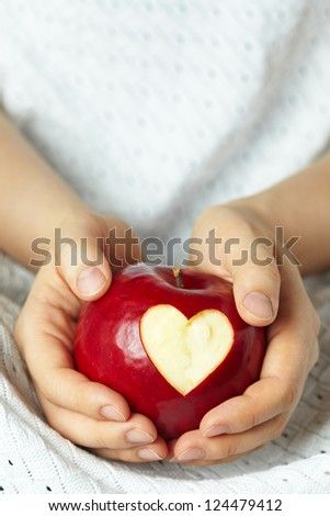 Woman's hand with apple, which cut a heart