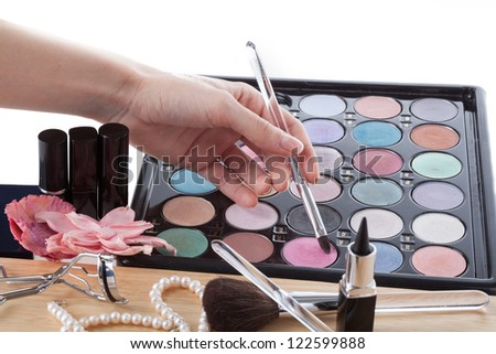 Woman's hand with brush and palette of colorful eye shadows