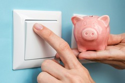 Woman's hand with piggy bank turns OFF electric lights at home. Savings on power supply, on utilities. Concept image.