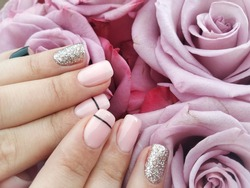 Woman's hand with pink and gold manicure holds  flower. Stylish fashionable woman's manicure. Nail polish. Artistic manicure. Modern style.