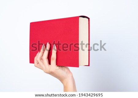 Woman's hand with pink manicure holding a red book, notebook, diary or sketch book. Education concept.  Photo stock ©