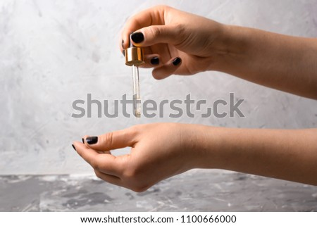 woman's hand with pipette and oil cosmetic product