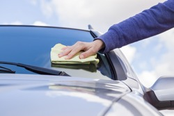 Woman's hand with rag cleaning a silver car's windshield on cloudy sky background in sunny day. Early spring washing or regular wash up. Professional car wash by hands.