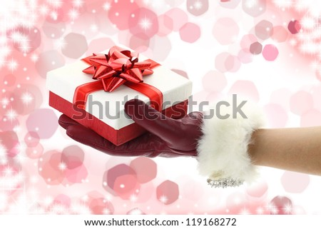 Woman\'s hand with red glove holding a Christmas gift