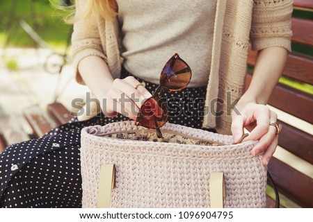 Woman's hand with sunglasses and knitted handbag. Stylish woman in gray shirt and knitted beige jacket sitting in the park with beige handbag. Street look, casual fashion concept  ストックフォト ©