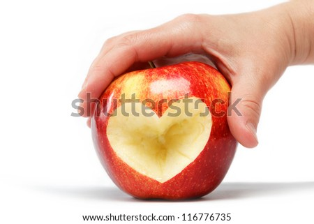 Woman's hand with the apple, which cut the heart on a white background.