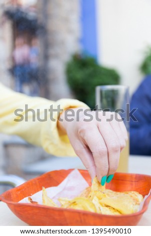 Woman's hand with yellow shirt and green painted fingernails pic