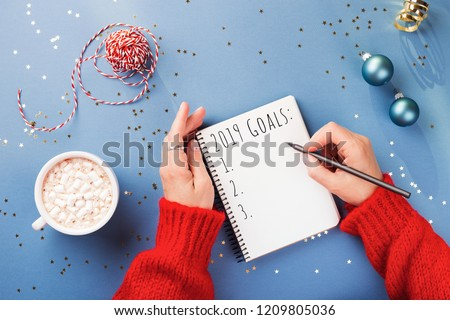 Woman's hand writing 2019 Goals in notebook decorated with Christmas decorations on the blue background. Top view. #1209805036