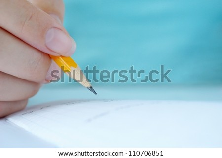 woman's hand writing in a notebook entry