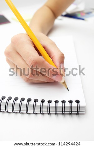 woman's hand writing in a notebook with a pen