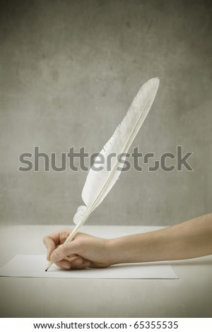 Woman's hand writing with a plume