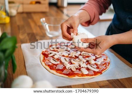 Woman's hands adding mozzarella cheese to a traditional margarita pizza. Preparation of a Original Italian pizza