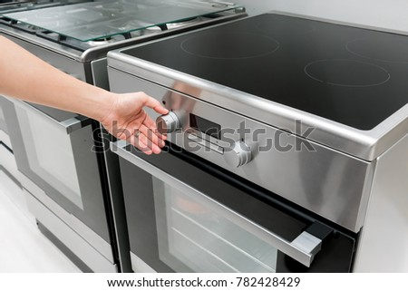 Woman's Hands adjusting heat button on black oven machine for cooking #782428429