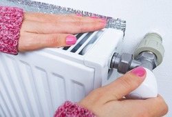 Woman's hands adjusting thermostat on heating radiator valve. Heating system at home, concept