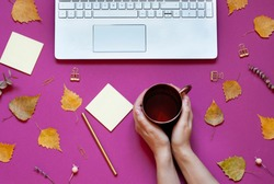 Woman's hands are holding a cup of tea on the conceptual autumn background. Fall business flat lay composition with a keyboard. Top view