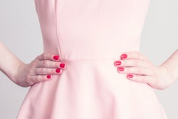 Woman's hands at the waist, close-up. The girl in the pink dress to be angry with someone, keeps hands on waist, cropped image, toned