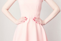 Woman's hands at the waist, close-up. The woman in the pink dress, keeps hands on waist, cropped image, toned