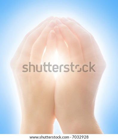 Woman's hands catching sunlight against clear blue sky