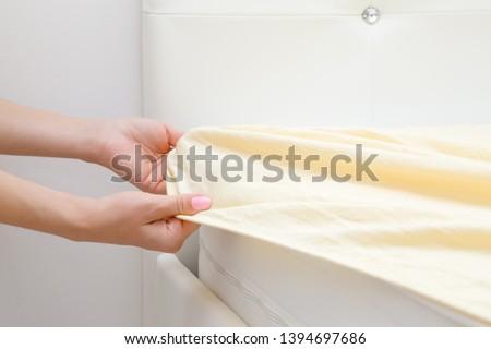 Woman's hands changing light yellow sheet on white mattress. Regular bed linen change. Closeup. Side view. #1394697686