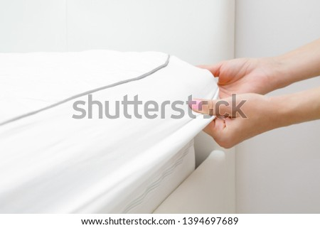 Woman's hands changing white mattress cover. Regular bed linen change. Closeup. #1394697689