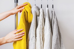 Woman's hands choosing yellow knitted sweater among others on hanger