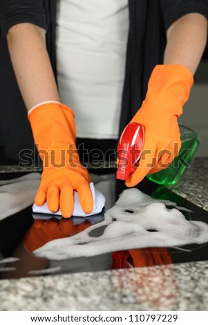Woman's hands cleaning a kitchen stove, closeup