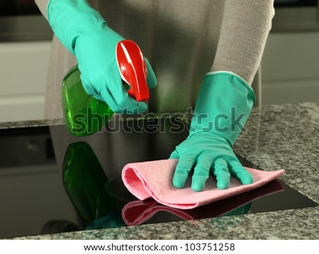 Woman's hands cleaning kitchen top in gloves