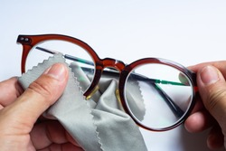 Woman's hands cleaning shortsighted or nearsighted eyeglasses by microfibre cleaning cloths, On white background, Close up & Macro shot, Selective focus, Optical concept