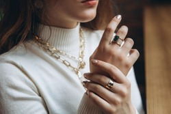 Woman's hands close up wearing rings and necklace modern accessories elegant lifestyle 2020