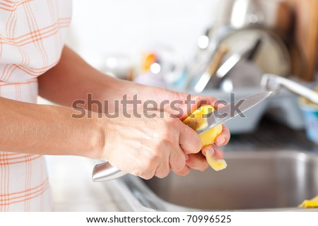 Woman's hands closeup, peeling potatoes in the kitchen