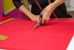 Woman's hands cutting bright red fabric on sketch lines with scissors. Preparing details of material for new, modern, classic dress, blouse, trousers or other clothes. Feminine hobby. Closeup.