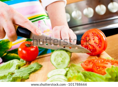 Woman's hands cutting cucumber, behind fresh vegetables.